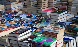 Stacks of colorful books displayed on a table.